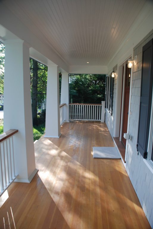 covered porch of shingle style home in new york by demotte architects