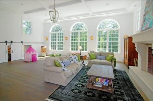 Family room with large windows in Westport CT home by DeMotte Architects