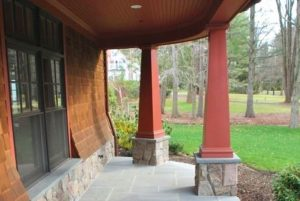 Front porch of shingle style home in NY by DeMotte Architects