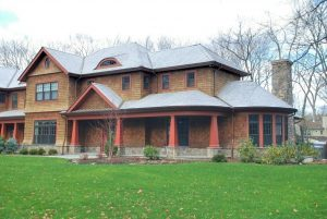 Home with cedar shingles, stone base, tapered bungalow columns