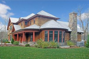 Shingle style home design with large windows by DeMotte Architects