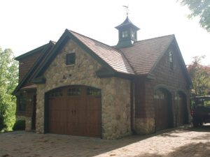 Shingle style home with stone veneer and carriage style garage doors in CT