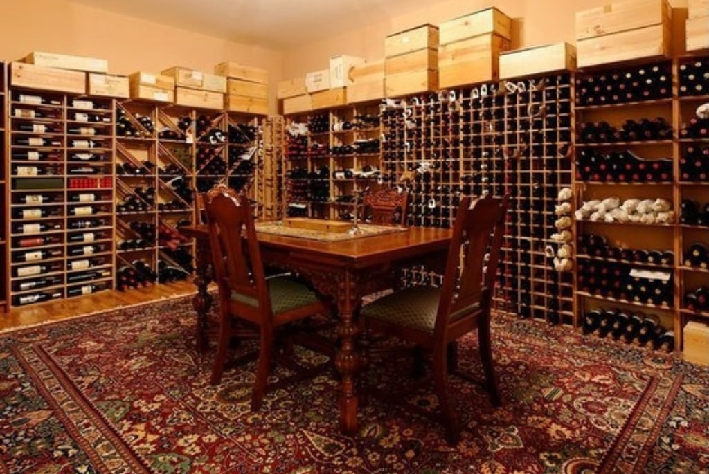 Traditional wine room in shingle style home in NY by DeMotte Architects