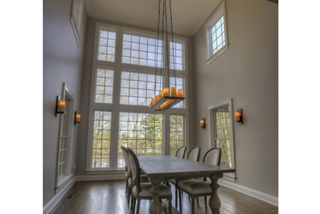 Beautiful dining room with large windows in NY home remodel by DeMotte Architects