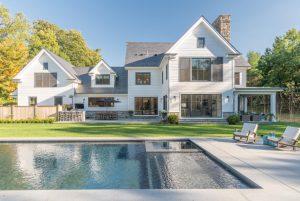 Backyard of modern farmhouse in Greenwich CT by DeMotte Architects