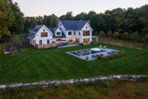 Connecticut modern farmhouse design with pool by DeMotte Architects